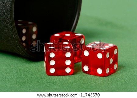 Red dice thrown from dice cup onto felt table - stock photo
