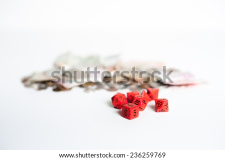Red dice with out of focus money in background - stock photo