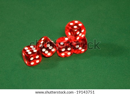 Red dices on the green table in the casino