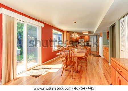 Red dining room interior with large wooden table and chairs. Has exit to the back yard. Northwest, USA