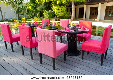 red dinning table set in the garden - stock photo