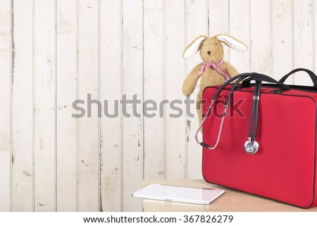 Red doctor bag, stethoscope, tablet-pc and soft toy - stock photo