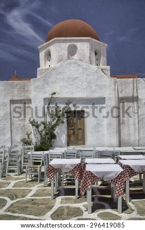 Red Domed Church in Mykonos, Greece with Tables and Chairs  - stock photo