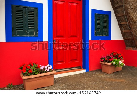 Red door and blue windows of a traditional cottage house in village of Santana, Madeira island, Portugal - stock photo