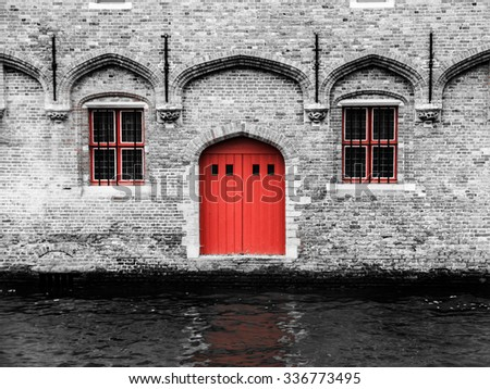 Red door and two windows at water canal. Typical architecture of Bruges, Belgium.