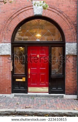 Red Door In Black Archway Door Frame with Windows on Brick Building - stock photo