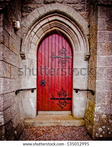 Red door on old church on snowy day - stock photo