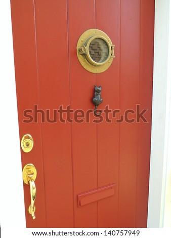 Red door with feline door knocker - stock photo