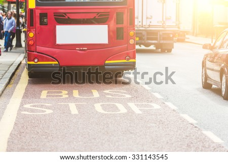 Red double-decker bus at bus stop in London. View from back, with focus on BUS writing on the road. on the left there are some persons and on the right some vehicles. Urban transport concept. - stock photo