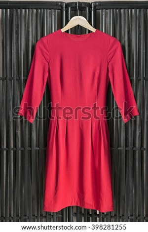 Red dress on clothes rack hanging on black bamboo screen - stock photo