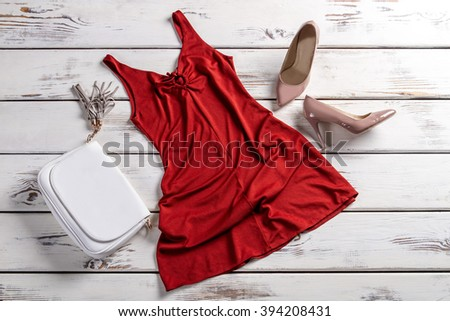 Red dress with clutch bag. Clothes and footwear on table. Fashionable garments for modern women. City girl's outfit. - stock photo