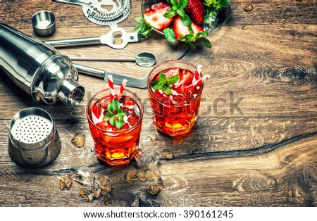 Red drink with ice. Cocktail making bar tools and shaker. Vintage style toned picture - stock photo
