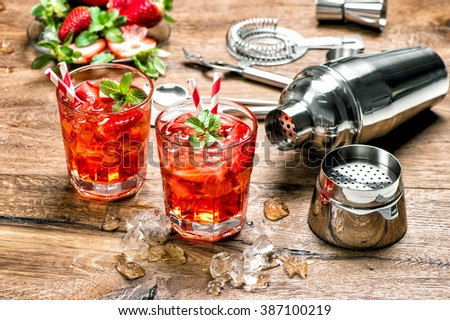 Red drink with ice. Cocktail making bar tools, strawberry and mint leaves