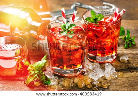 Red drink with strawberry, mint leaves, ice. Cocktail bar with party lights - stock photo