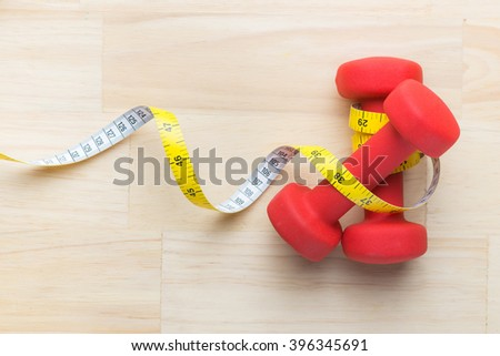 Red dumbbells and measure tape for using in fitness, concept for slimming and healthy lifestyle. Fitness weight loss diet nutrition - stock photo