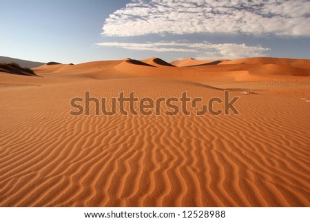 Red dunes against blue clear sky with cloudscape. Sossusvlei. Namib desert. Namibia. - stock photo