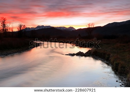 Red dusk sky above the Provo River, Utah, USA. - stock photo