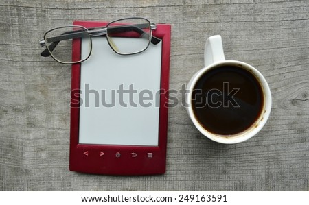 red e-book,Notepad,read ing glasses,hot Cup of coffee on wooden background - stock photo