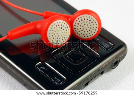 Red earphones on a MP3 player concepts of music download and piracy - stock photo