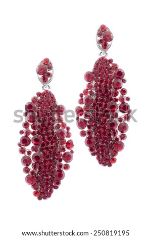 Red earrings inlaid with precious stones on a white background - stock photo