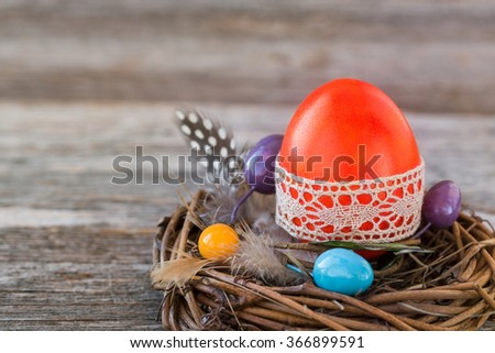 Red Easter egg decorated with lace in small nest on wooden background - stock photo