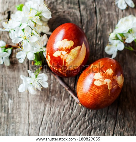 Red Easter Eggs Decorated with Fresh Cherry Flowers and Onions Peels - stock photo