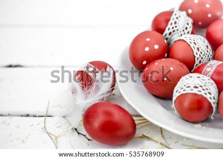 Red Easter eggs on a white plate and on white background tied lace tape , close-up , lie on wooden background, still life