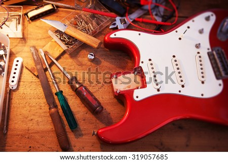 Red electric guitar body on guitar repair desk or in a repair work shop. Neck and pickguard detached. Double cutaway solid body guitar, red metallic color. Shallow depth of field. - stock photo
