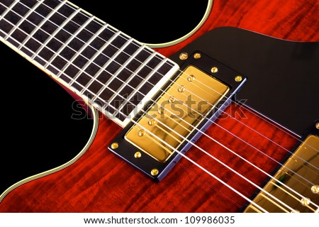 red electric guitar isolated on black background, closeup - stock photo