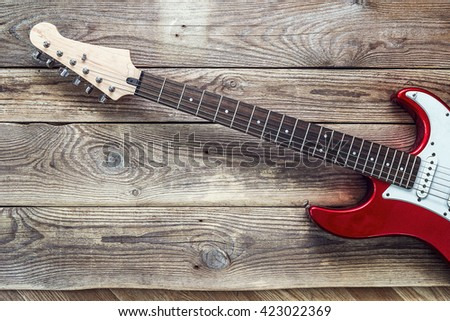 Red electric guitar on grunge wooden planks background. Place for text. Top view - stock photo