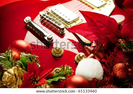 Red electric guitar with christmas ornaments. Concept image for christmas / holiday season music event, or musical instrument for christmas present. - stock photo