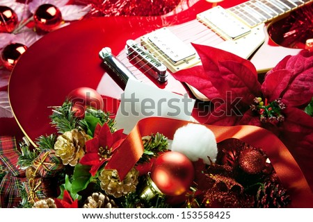 Red electric guitar with white blank card in front for your message. Concept image for holiday musical event.  - stock photo