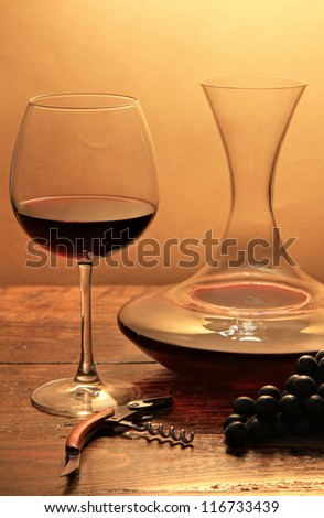 Red elegant wine glass and filled decanter. On wood with warm back light