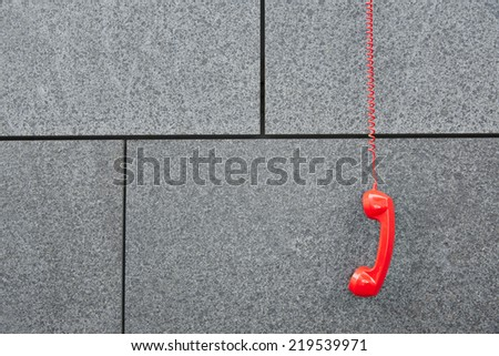 Red emercency call phone hanging down on a wall - stock photo