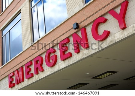 Red emergency room sign on the side of hospital with windows - stock photo