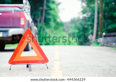 Red emergency stop sign and broken red pickup car on the jungle road, A Truck with a breakdown alongside the road.  - stock photo