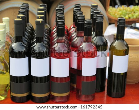 Red empty label wine bottles stacked in rows with barrels and grapes in background - stock photo