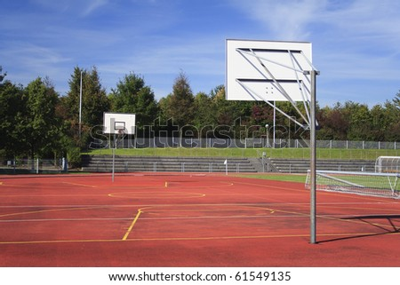 Red, empty outdoor basketball field with trees - stock photo