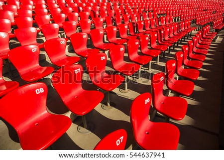 Red empty stadium chairs under the sun with nobody