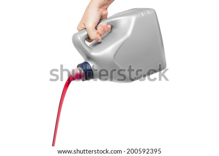 Red engine oil pouring from a canister in hand isolated on white background - stock photo