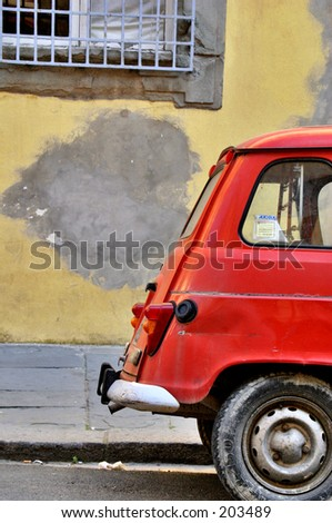 Red European automobile in front of a yellow building - stock photo