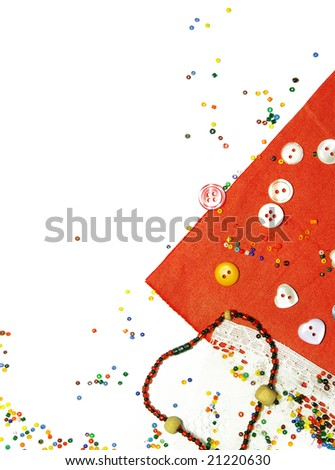 Red fabric, buttons and colorful beads as background - stock photo