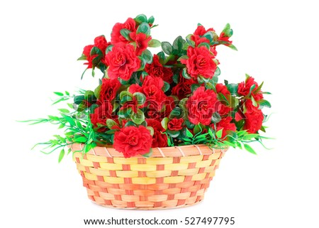Red fabric flowers in wicker basket isolated on white background.