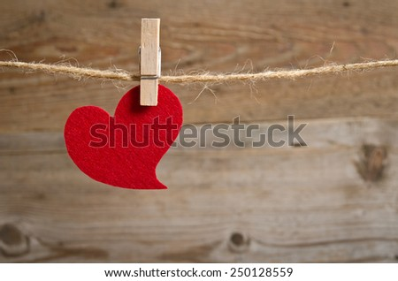 Red fabric heart hanging on the clothesline . On wooden background - stock photo
