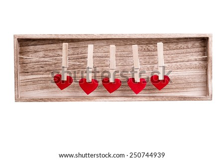 Red fabric heart hanging on the clothesline, on wooden background. Love concept - stock photo