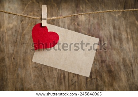 Red fabric heart with sheet of paper hanging on the clothesline. On old wood background.  - stock photo
