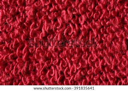 Red fabric with structured and knitted fibres extreme close up. Fabric texture. Fabric background. Knitted fabric texture. - stock photo