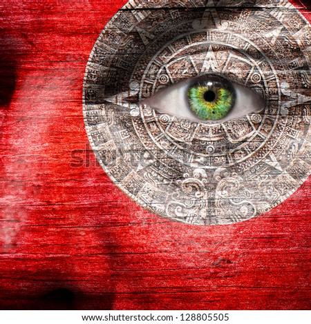 Red face with Mayan Calendar centered around the green eye - stock photo