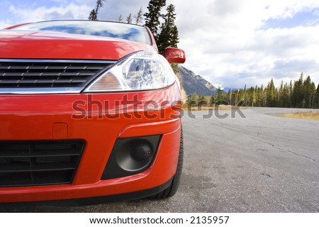 Red family car parked in a mountain rest area