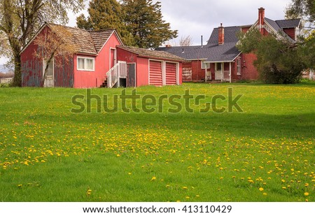 Red farm house and outbuildings on a farm in rural Utah, USA. - stock photo